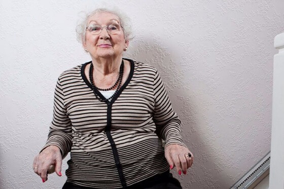 elderly woman using a stairlift