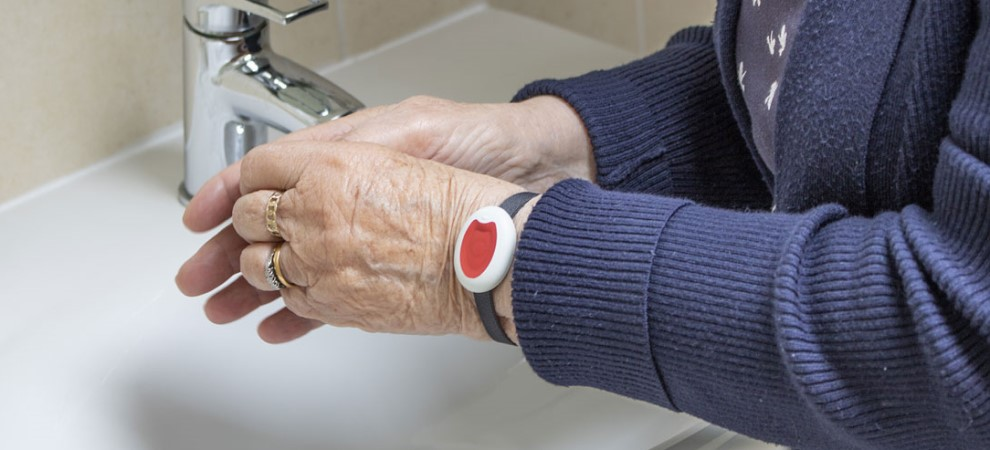 Woman washing her hands while wearing a Pendant Alarm on her wrist