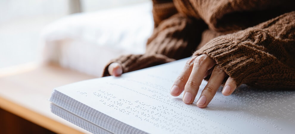 a blind person reading a braille book